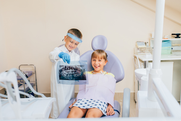 Boy dressed like a dentist showing teeth x-ray to male patient in dental hospital.