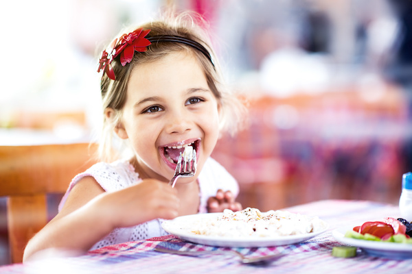 Little Girl Having Her Meal With Pleasure