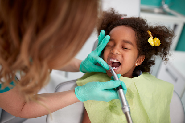 Female dentist patiently polish teeth to child